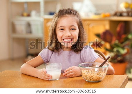 funny shot of a little girl having breakfast: milk mustache
