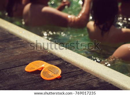 Funny shutter shading sunglasses of orange color extravagant party goggles retro style near swimming pool with people #769017235