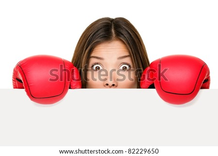 Funny sign woman hiding scared and afraid behind blank empty paper sign board edge wearing boxing gloves. Young Asian business woman isolated on white background.