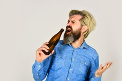 funny singer. beer and football. relax after working day. lets have fun. bearded man has hangover. mature man drink beer. healthy water in glass bottle. brutal hipster drinking alcohol beverage.