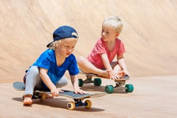 Funny skateboard riding. Little children with skateboards have fun in beach skate park. Active family lifestyle, outdoor activities on summer holidays in city. Kids recreational sports.
