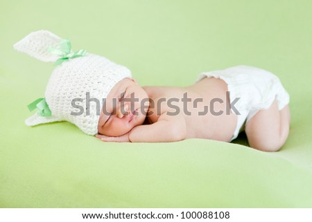 Funny sleeping newborn child. Bunny cap on head of girl.