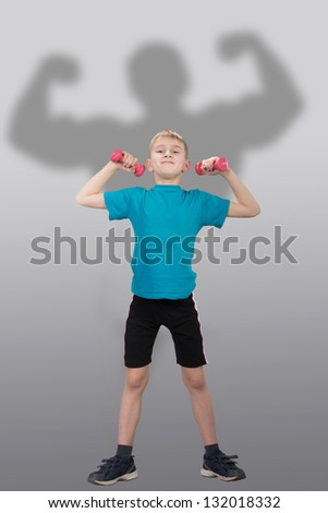 Funny slim boy with bodybuilder's silhouette behind him