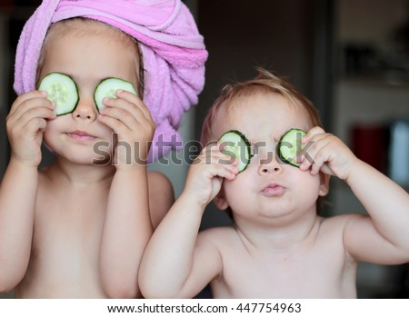 Funny small girl with a bath towel on her head and her small brother holding a piece of cucumber on their eyes like a mask, beauty and health concept, indoor closeup portrait