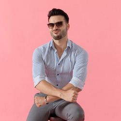 Funny smart casual man maxing a duck face and holding his hands in a x shape, sitting on a stool on pink studio background