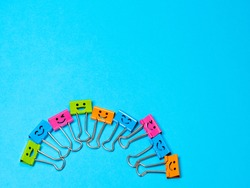 Funny smile metal binder clip or multicolored paperclip on blue background with copyspace for text