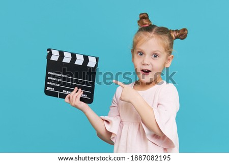Funny smiling child girl hold film making clapperboard isolated on blue background. Little clipmaker, acting training. Funny face. Copy space for text. Photo stock ©