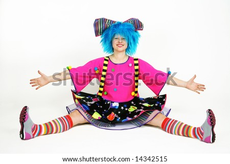 Funny smiling clown with blue hair sitting on the floor
