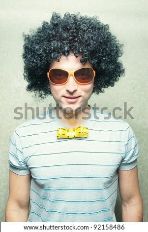 funny smiling guy in afro curly wig with eyeglasses and ribbon bowtie