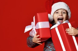 Funny smiling joyful  child boy in Santa red hat holding Christmas gift in hand over the red background