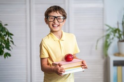 Funny smiling little boy with glasses. Happy schoolboy with books and an Apple in his hands. Back to school. The child is happy to learn. Thirst for knowledge.