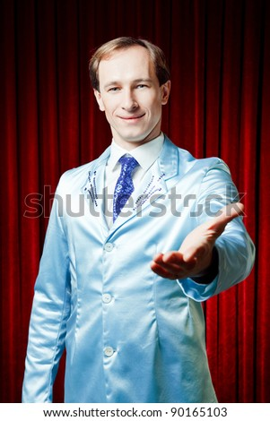 Funny smiling man dressed in a blue suite for a party showing his hand presenting something on a red background - stock photo