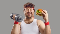 Funny smiling man with dumbbell and delicious burger looking at camera. Happy fat guy holding free weights and eating big yummy hamburger. Sport, food, failed diet, workout exercise, cheat day concept