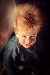 Funny smiling red haired little boy with electrified hair like big dandelion. Image with selective focus and toning