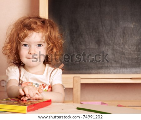 Funny smiling schoolchild in a class against blackboard