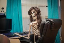 Funny smiling skeleton sitting  in room behind the desktop computer