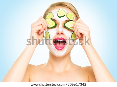 Funny smiling Spa Woman applying fresh Facial Mask with cucumbers. Beauty Treatments. Face mask, skin care concept. Beautiful Woman Applying Natural Homemade Facial Mask