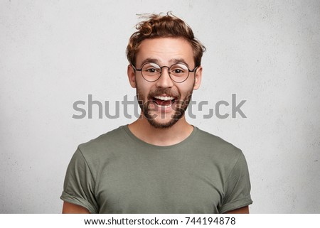 Funny smiling unshaven male wonk wears round spectacles and casual clothes, being glad to recieve interesting book as present, expresses positive emotions. People, happiness, positiveness concept #744194878
