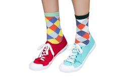Funny sneakers and socks. Colorful different sneakers on an isolated background. Funny legs in different sneakers and socks.