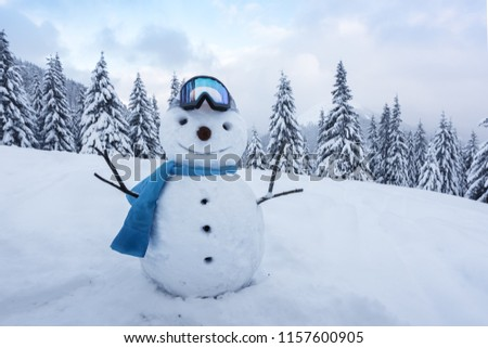 Funny snowman in ski glass in snowy mountains. Ski resort concept. Merry Christmass and happy New Year!