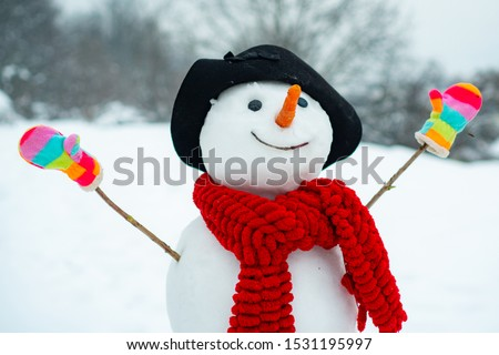 Funny snowman in stylish hat and scarf on snowy field. The morning before Christmas. Funny snowmen. Snowman with a bag of gifts. Snowman is standing in winter hat and scarf with red nose.