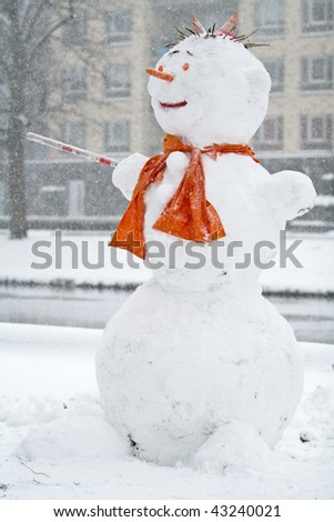Funny snowman with orange scarf made of fresh snow during snowfall