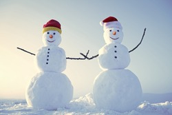 funny snowmen. Snowman couple outdoor. Christmas or xmas decoration. New year snowmen from snow in santa hat. Happy holiday and celebration. Santa claus hat in winter.