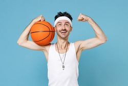 Funny sporty man basketball player with thin skinny body sportsman in headband shirt shorts whistle hold ball showing biceps muscles isolated on blue background. Workout gym sport motivation concept