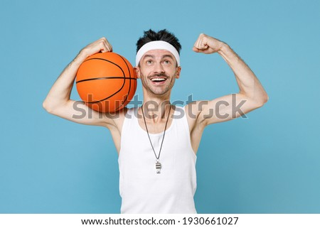 Funny sporty man basketball player with thin skinny body sportsman in headband shirt shorts whistle hold ball showing biceps muscles isolated on blue background. Workout gym sport motivation concept Foto stock ©