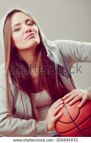 Funny sporty teenager girl wearing hooded sweatshirt holding basketball. Teen sport. Face expression.