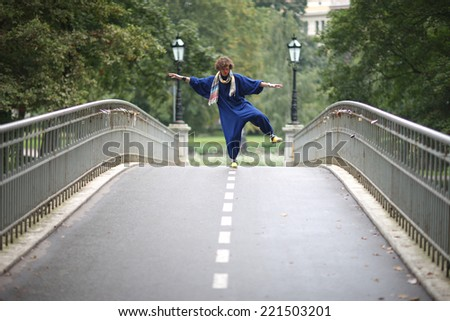 Funny street clown standing on one leg balancing; city park theater