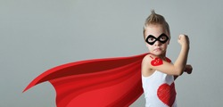 Funny strong child raising hand in success gesture. Little cool boy superhero loves mom, shows heart. Portrait confident kid in costume super hero expresses strength, leadership. banner, copy space.