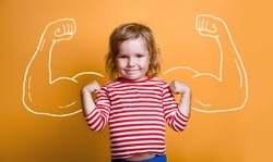 Funny strong child with muscles over yellow wall. Nerd kindergarten kid girl showing bicep muscles. Dream, confidence, success, possible, innovation. Go back elementary school.