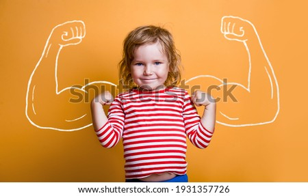 Funny strong child with muscles over yellow wall. Nerd kindergarten kid girl showing bicep muscles. Dream, confidence, success, possible, innovation. Go back elementary school. Foto stock ©