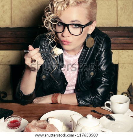funny stylish blonde girl with great hairdo in glasses and black jacket eating cake in the cafe. indoor shot