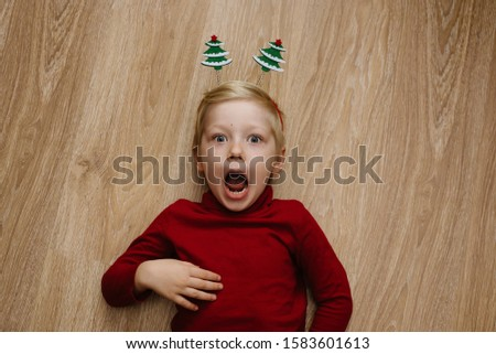 Funny surprised joyful blond caucasian child boy with Christmas tree hoop on his head is laying on the floor. Christmas, winter, New Year concept. Place for text. Place for text #1583601613
