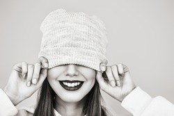 Funny teen girl smiles pulling her cap over her eyes. Youth style, fashion. Studio monochrome portrait.