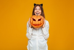 Funny teenage schoolgirl in uniform holding halloween pumpkin and laughing isolated over orange background