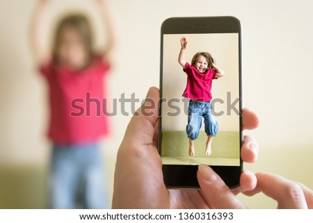 Funny three-year-old child jump on couch. Mother taking photo of baby girl with her mobile phone. Photography of happy kid playing and jumping at home. Adorable toddler with long hair dances on sofa.