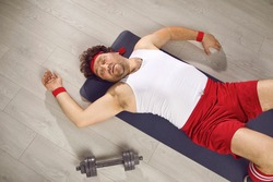 Funny tired fat man lying on fitness mat after gym workout. Exhausted guy in retro sweatband, tank top and shorts fallen on floor after sports exercise with dumbbells. Top view, high angle, from above