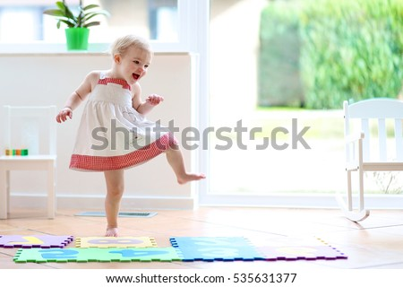 Funny toddler girl dancing indoors. Little child having fun moving and jumping in a sunny white room at home or kindergarten stock photo