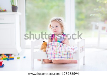 Funny toddler girl feeding her toy bear in a sunny room with big garden view windows