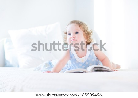 Funny toddler girl in a blue dress reading a book on a white bed