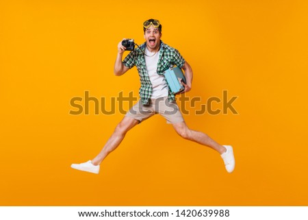 Funny tourist guy in summer outfit holding retro camera and blue suitcase. Man in diving mask jumping on orange background