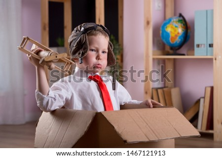 Funny weird face child boy playing with toy airplane. Nerd pupil pilot in class of kindergarten or preschool. Success, innovation technology, education, genius. Back to school.