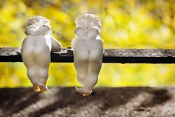 Funny white ceramic angels with small wings are back view in autumn park.