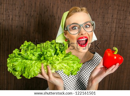 Funny woman cook holding salad and sweet pepper, close up of a housewife