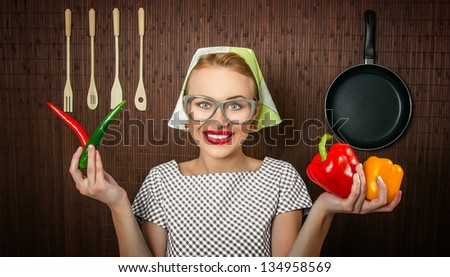 Funny woman cook holding sweet and hot pepper