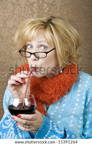 Funny woman drinking wine through a straw