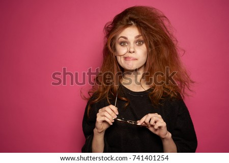 funny woman in a hand glasses on a pink background, beauty